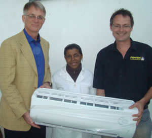 Rotary President Volker Biebesheimer and Chris Blackburn presenting the air conditioning unit to Sra Lidia Costa