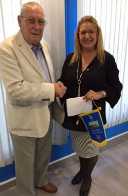 Chris Ireland, president of afpop's Management Council receiving the cheque from Manuela Robinson, president of the Rotary club.