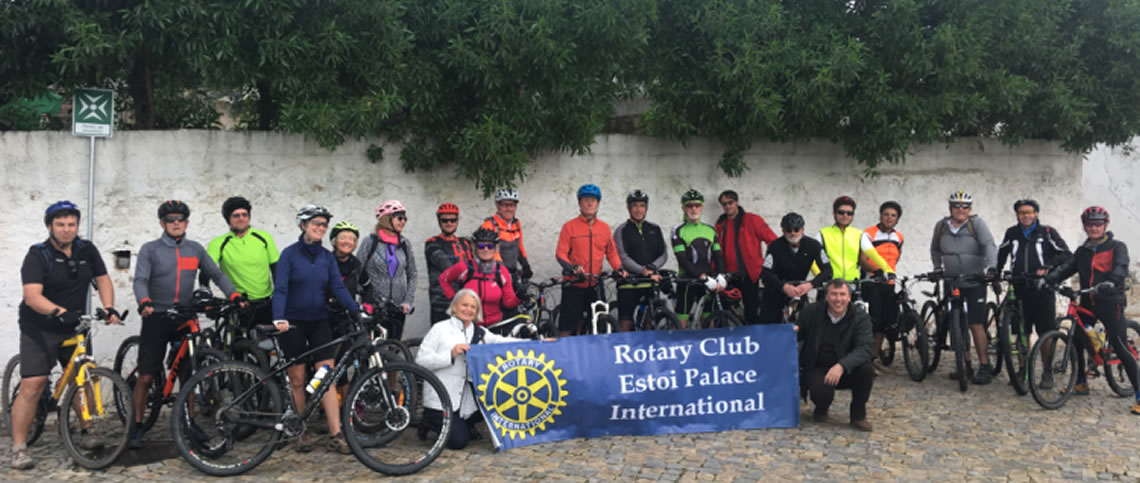 Activity Bike Ride Group plus Christine Fay and Vitor Rosao from RC Estoi Palace International, kneeling holding the banner.